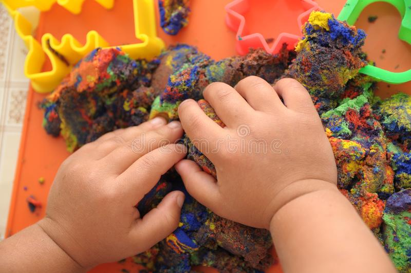 Mani del bambino che giocano sabbia cinetica multicolore giocattolo del gioco di attività dei bambini per arte di formazione di m immagini stock libere da diritti