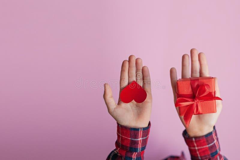 Mani del bambino che tengono il presente di carta rosso della scatola e del cuore in mani su fondo rosa Concetto di giorno dei bi immagine stock libera da diritti
