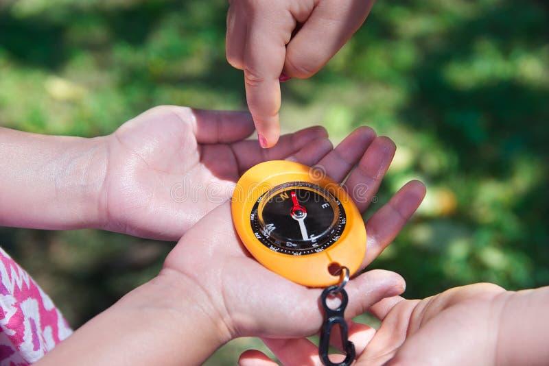 Mani del bambino che tengono una bussola in un gioco geocaching Sport all'aperto nella natura con lo spazio vuoto della copia fotografia stock libera da diritti