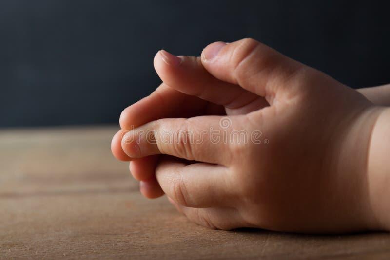 Mani del bambino piegate per la preghiera fotografia stock libera da diritti