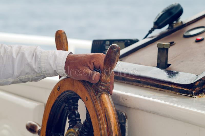 Mani del capitano che tiene la ruota sulla piattaforma della nave immagini stock
