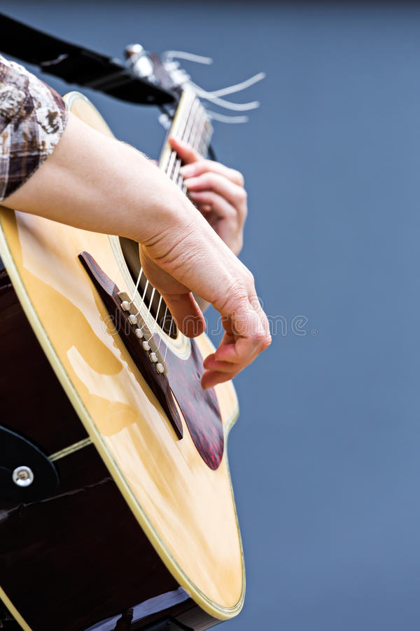 Mani del chitarrista che giocano il primo piano della chitarra acustica fotografie stock