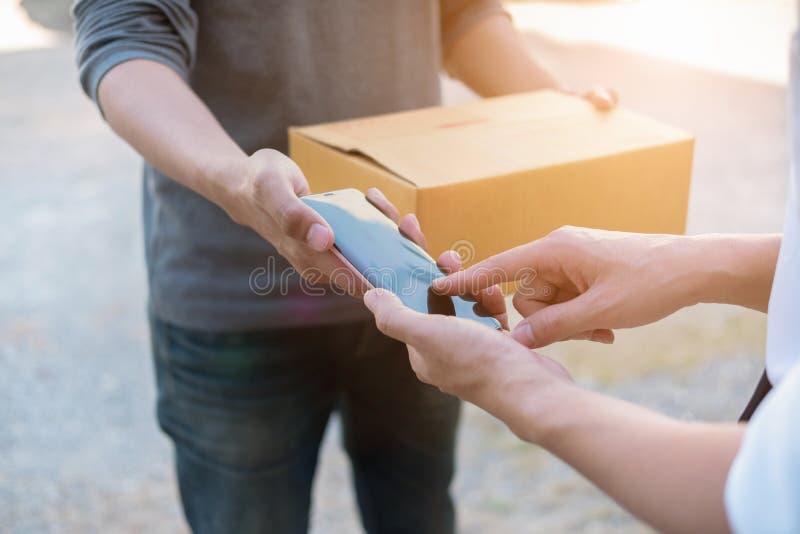 Mani del cliente che aggiungono firma in telefono cellulare, uomo che riceve la scatola del servizio pacchi postali dal corriere  fotografia stock