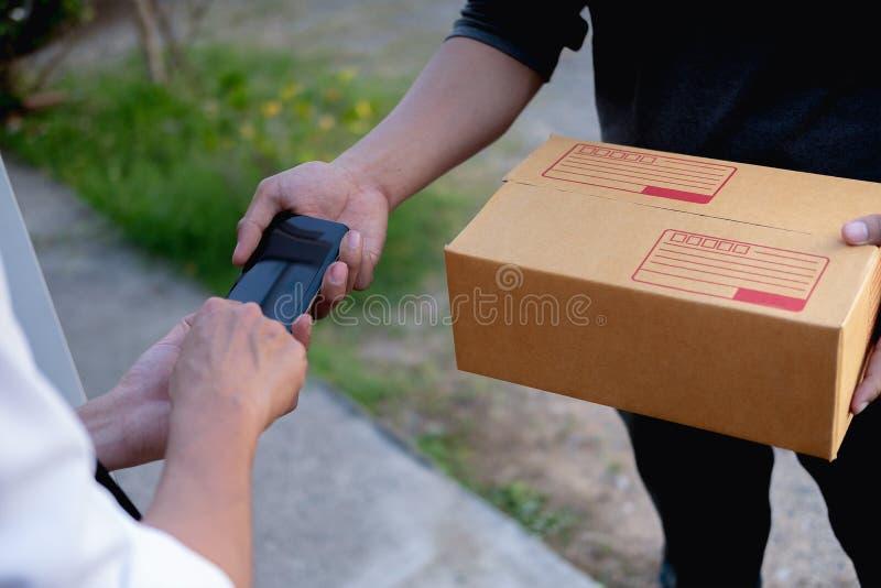 Mani del cliente che aggiungono firma in telefono cellulare, uomo che riceve la scatola del servizio pacchi postali dal corriere  fotografie stock libere da diritti