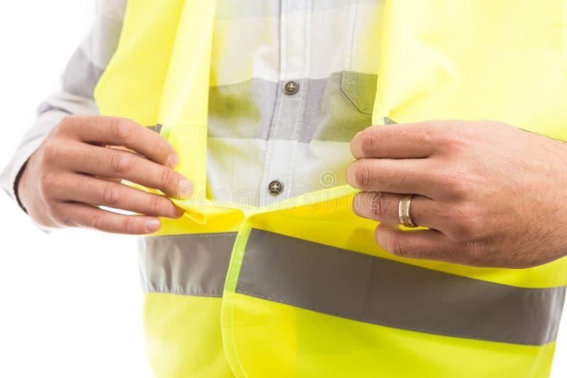 Mani del costruttore che chiudono la maglia protettiva riflettente del velcro fotografie stock