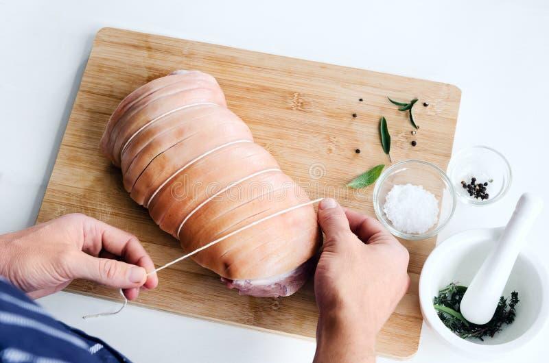 Mani del cuoco unico con l'arrosto di carne di maiale della carne cruda che cucina preparazione fotografia stock libera da diritti