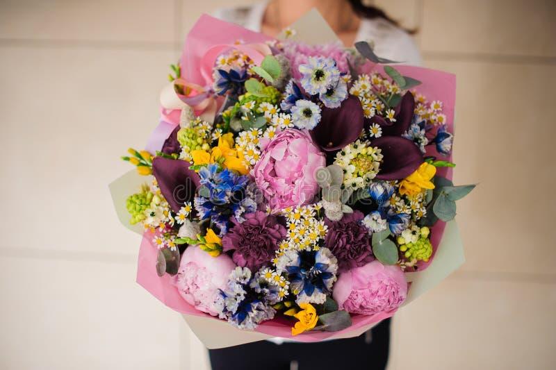 Mani del fiorista con il grande mazzo floreale fotografia stock