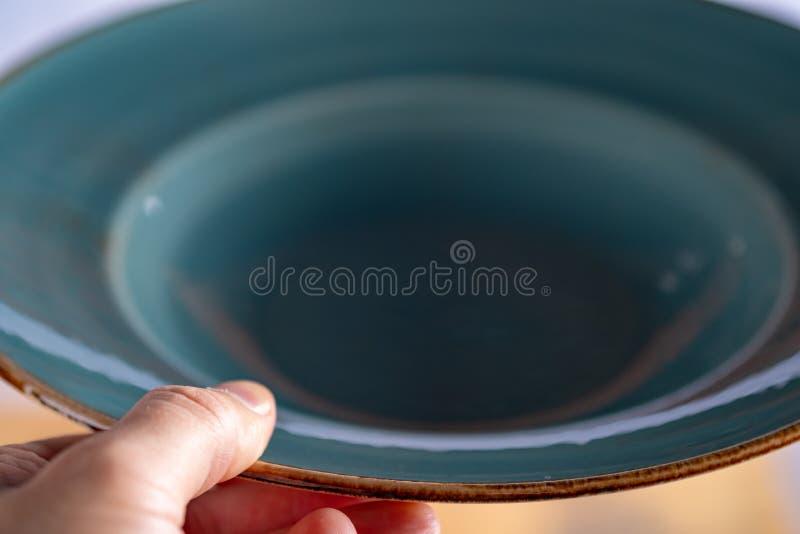 Mani del fotografo che tengono piatto blu vuoto fotografia stock