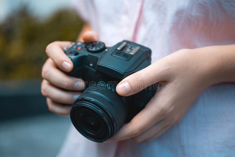 Mani del fotografo che tengono una macchina fotografica digitale, mettenti a fuoco e prendenti le foto, macro primo piano immagini stock libere da diritti