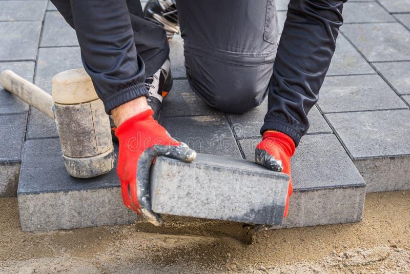 Mani del lavoratore che installano i blocchetti di calcestruzzo del lastricatore con il martello di gomma immagine stock libera da diritti