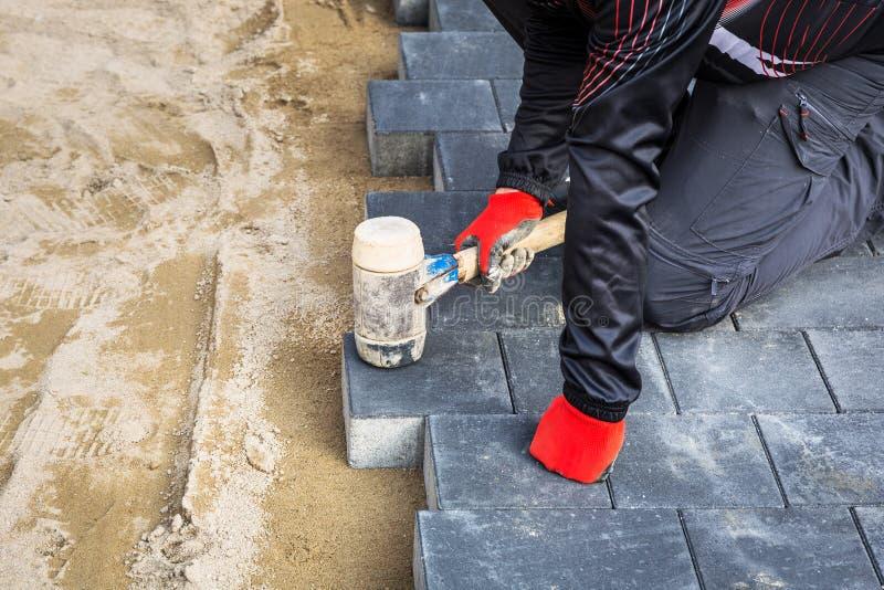 Mani del lavoratore che installano i blocchetti di calcestruzzo del lastricatore con il martello di gomma fotografia stock
