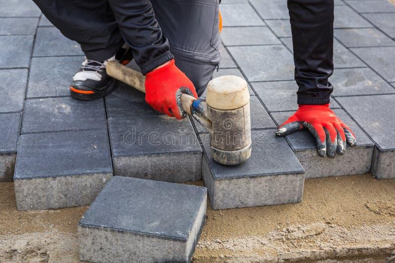Mani del lavoratore che installano i blocchetti di calcestruzzo del lastricatore con il martello di gomma fotografie stock libere da diritti