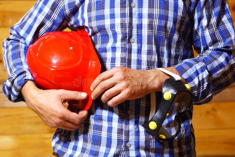 Mani del lavoratore con il casco fotografia stock libera da diritti