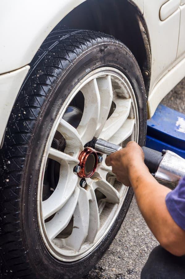 Mani del meccanico con il pneumatico cambiante dello strumento dell'automobile immagine stock libera da diritti