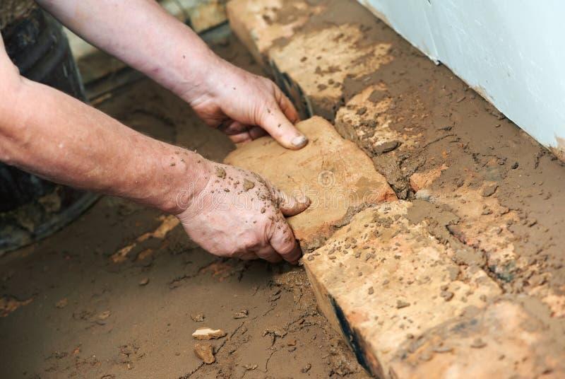 Mani del muratore agli impianti di lavoro di muratura immagine stock