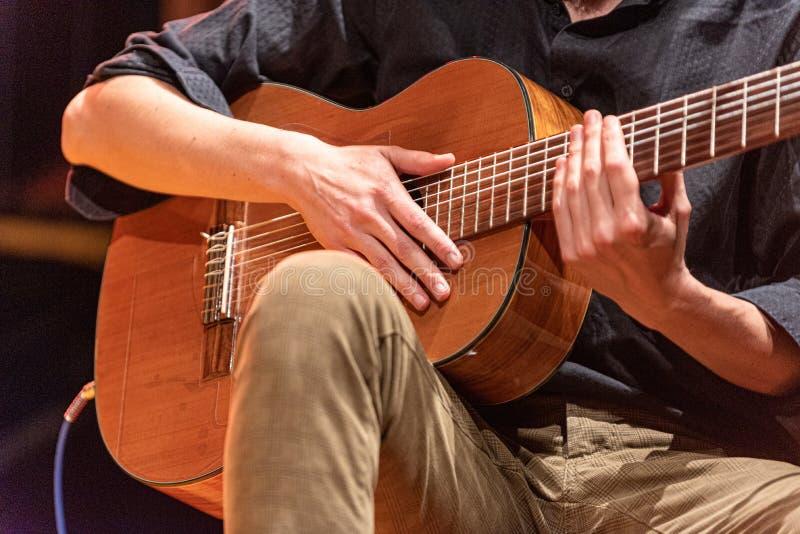 Mani del musicista che giocano una chitarra brasiliana di 7 corde su una fase immagine stock