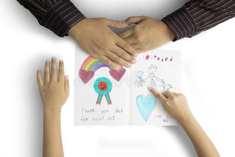 Mani del padre e del bambino con la cartolina d'auguri fotografia stock