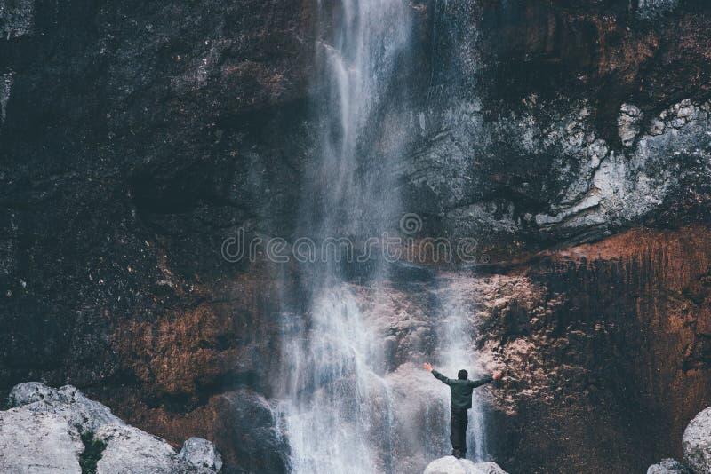 Mani del paesaggio e del viaggiatore della cascata sollevate fotografia stock