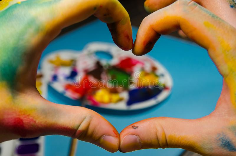 Mani del pittore che fanno un cuore fotografie stock libere da diritti