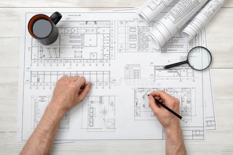 Mani del primo piano dell'architetto che funzionano con un disegno fotografia stock libera da diritti