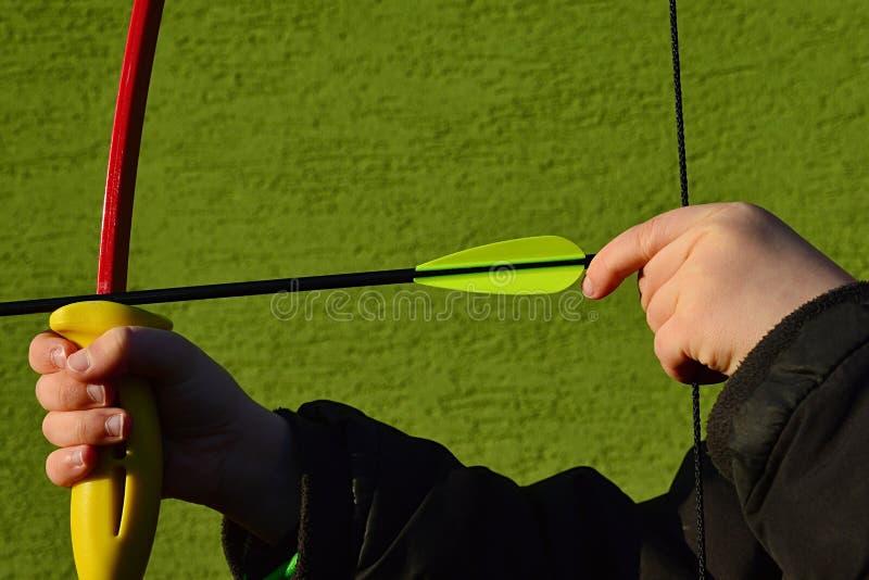 Mani del ragazzo che provano a fare stile di tiraggio di pizzico della corda di arco, tendentesi con la mano sinistra fotografie stock libere da diritti