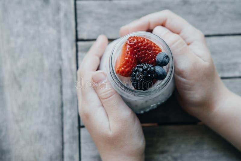 Mani del ragazzo con budino con i semi di chia, il yogurt e la frutta fresca: immagini stock