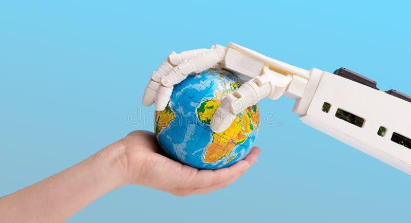 Mani del robot e dell'essere umano che tengono il globo della terra immagine stock libera da diritti