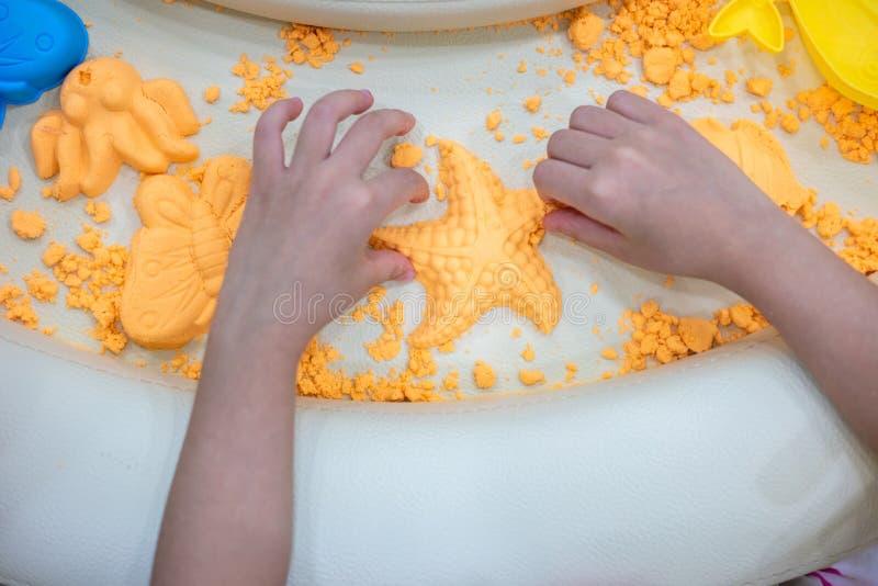 Mani del ` s dei bambini che giocano sabbia cinetica fotografia stock