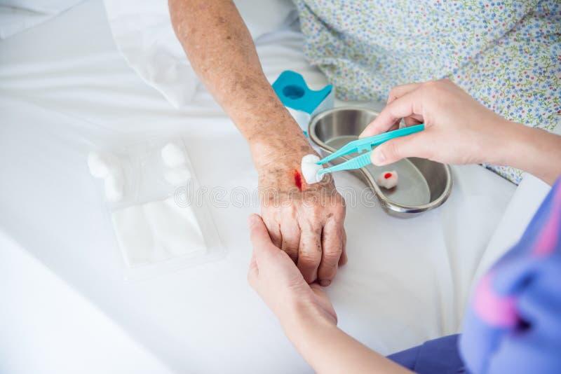 Mani del ` s dell'infermiere che vestono ferita per la mano paziente del ` s fotografia stock