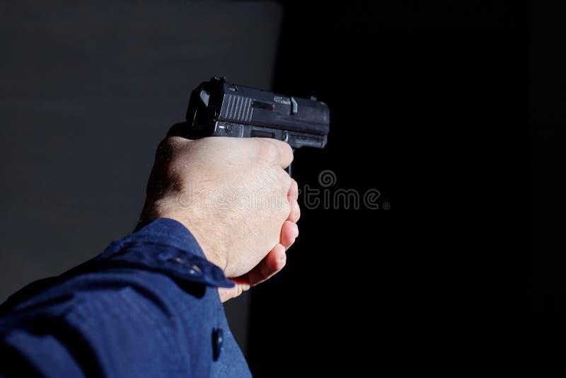 Mani del ` s dell'ufficiale di polizia che tendono con la pistola fotografia stock