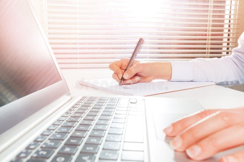 Mani del ` s della donna facendo uso del computer portatile e della scrittura sul blocco note immagini stock libere da diritti