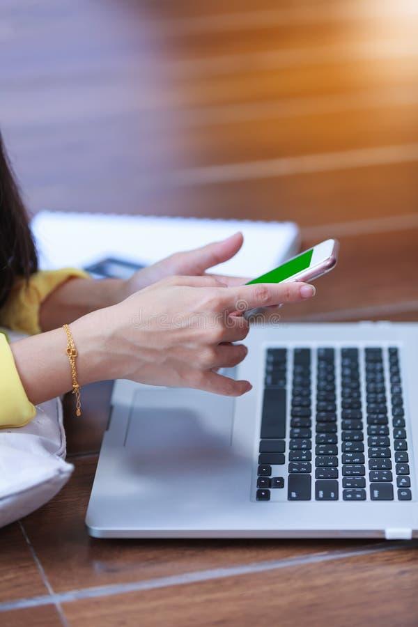 Mani del ` s della donna facendo uso del telefono cellulare e del computer portatile sul legno del pavimento fotografia stock