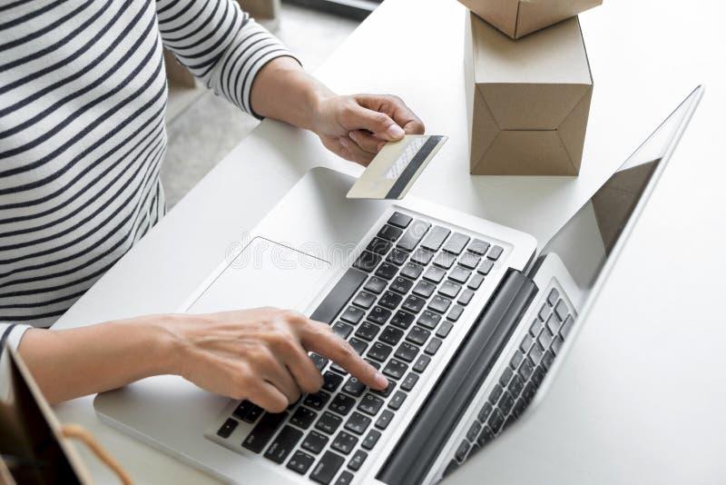 Mani del ` s della donna facendo uso del registro della carta di credito e dello sho online di pagamenti immagini stock libere da diritti