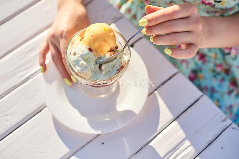 Mani del ` s della ragazza del primo piano che che mangiano le palle di un gelato in una ciotola fotografie stock