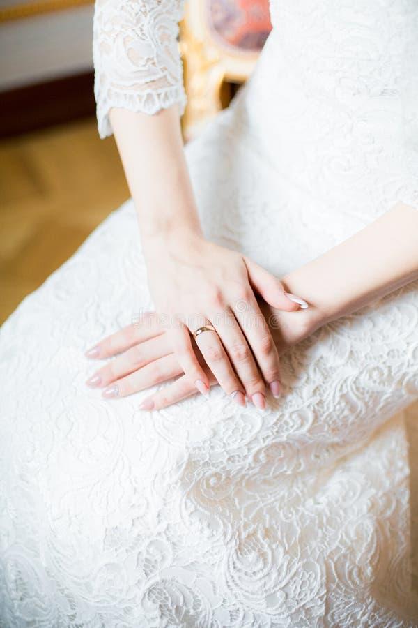 Mani del ` s della sposa sul bello vestito da sposa bianco fotografia stock libera da diritti