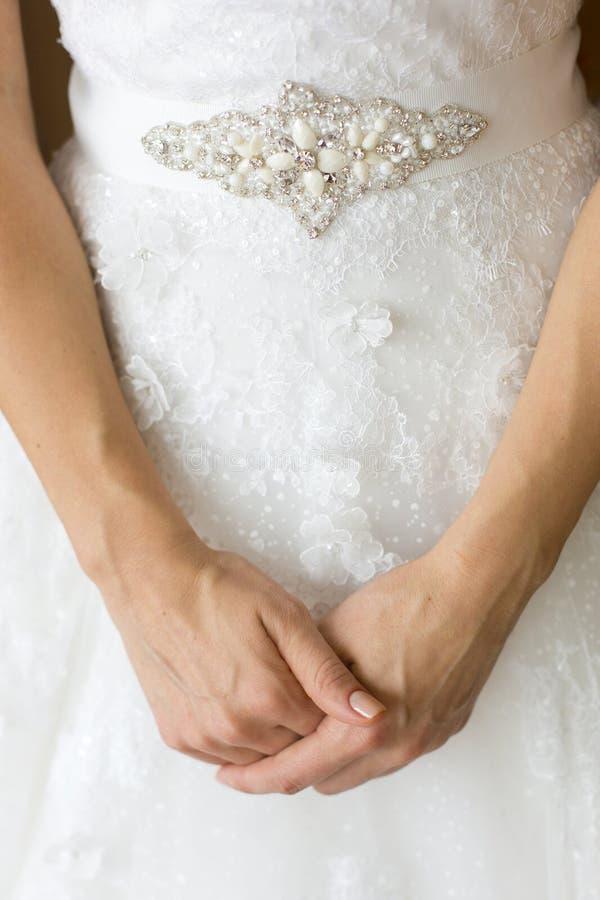 Mani del ` s della sposa sul vestito da sposa dal pizzo con la cinghia ricamata decorativa fotografie stock libere da diritti