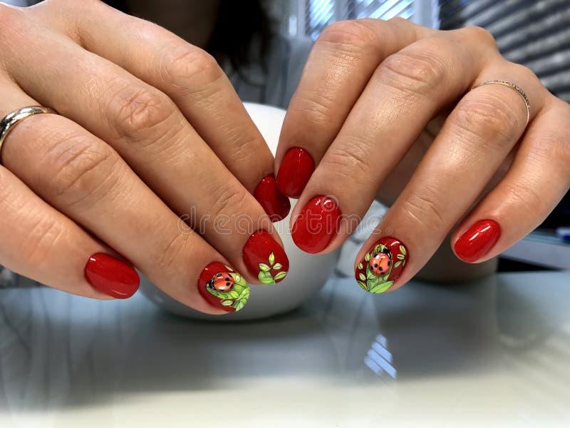 Mani del ` s delle donne con il manicure rosso e la progettazione interessante immagine stock libera da diritti