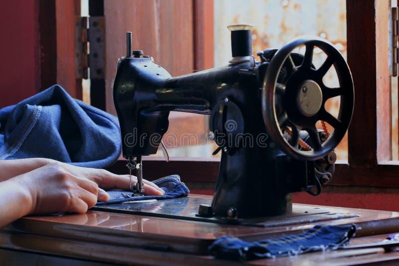 Mani del ` s delle donne della cucitrice che usando macchina per cucire fotografia stock