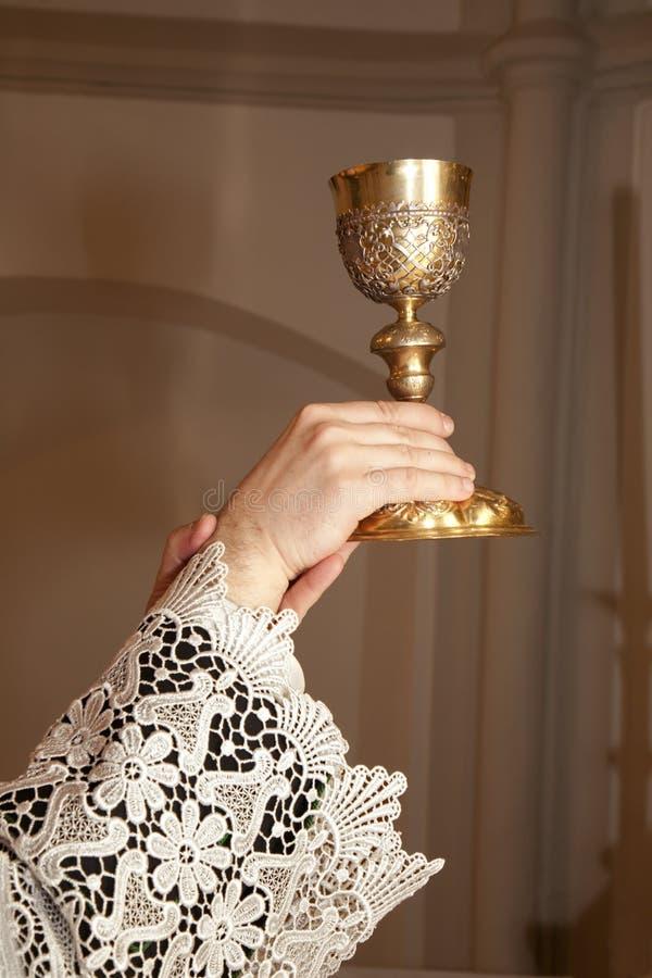 Mani del sacerdote dalla massa immagini stock libere da diritti