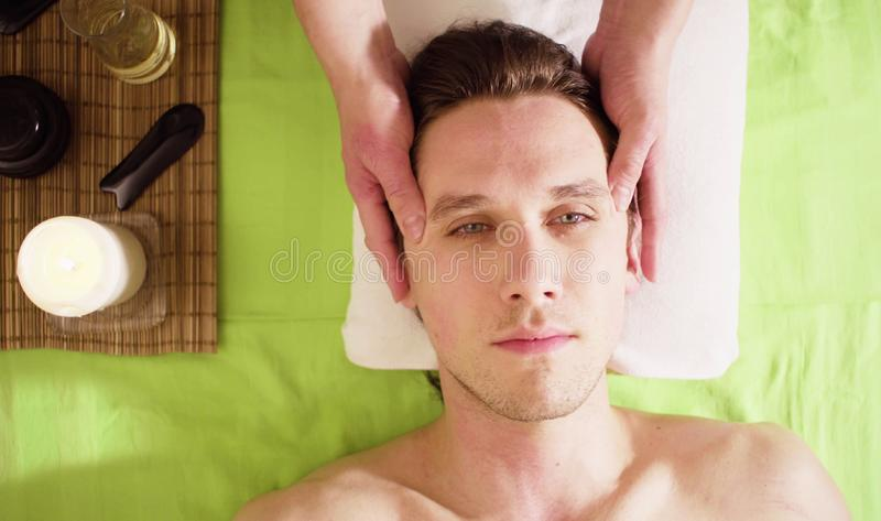 Mani del terapista che fanno massaggio del fronte maschio fotografia stock