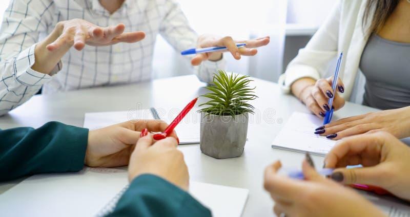 Mani del tipo del primo piano e della studentessa con le penne e taccuini sulla tavola fotografie stock libere da diritti