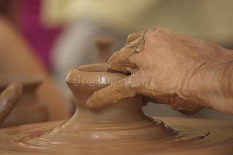 Mani del vasaio che funzionano l'argilla fotografia stock