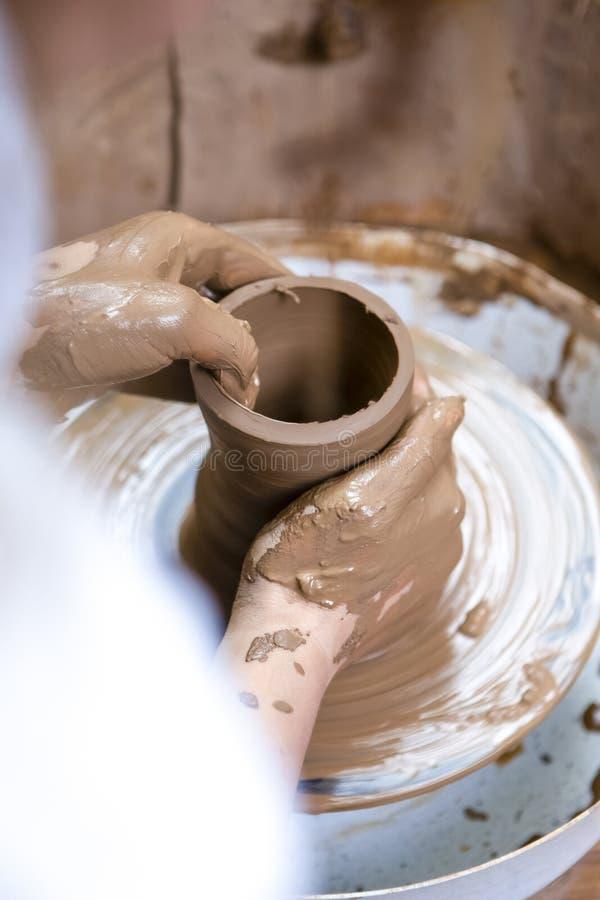 Mani del vasaio femminile con esperienza che lavora con Clay Lump sul gruppo di lavoro del tornio da vasaio dentro fotografie stock