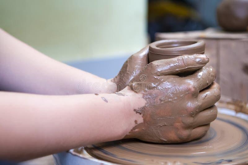 Mani del vasaio femminile con esperienza che lavora con Clay Lump sul gruppo di lavoro del tornio da vasaio dentro immagine stock