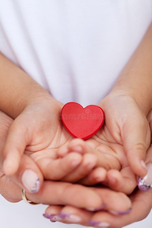 Mani dell'adulto e del bambino che tengono cuore rosso fotografia stock libera da diritti