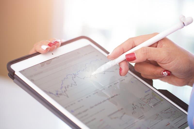 Mani dell'affare che analizzano le statistiche finanziarie visualizzate sullo schermo della compressa immagine stock