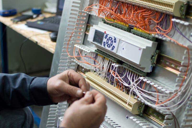 Mani dell'elettricista che montano il gruppo di regolazione industriale di HVAC nell'officina Foto del primo piano fotografia stock libera da diritti