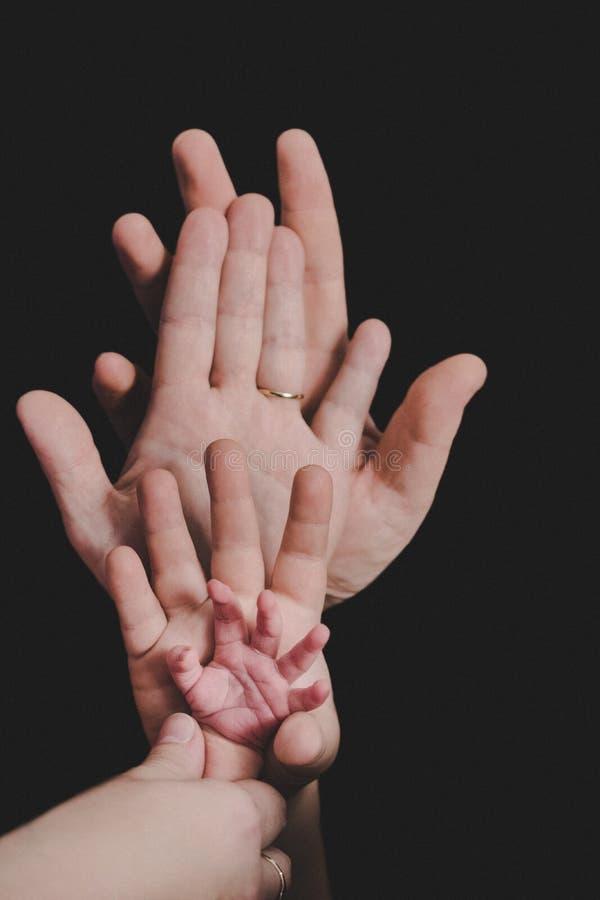 Mani dell'intera famiglia Padre, madre, figlio e un bambino Famiglia felice amichevole fotografia stock libera da diritti