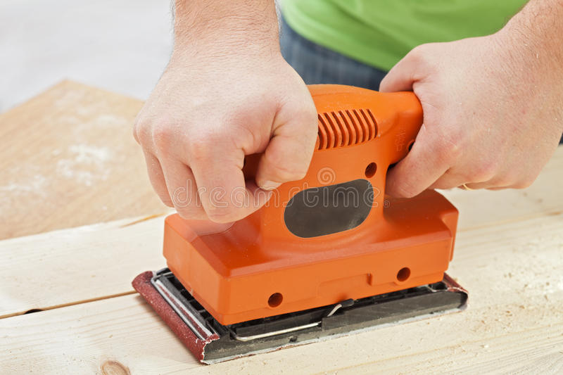Mani dell'operaio con la macchina della sabbiatrice elettrica immagine stock libera da diritti