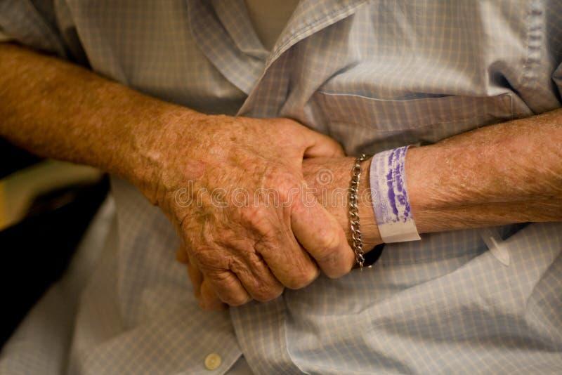 Mani dell'uomo anziano con il wristband dell'ospedale immagini stock libere da diritti